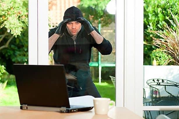 Burglar-looking-at-laptop-through-window